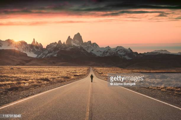 man walking alone on the road to fitz roy, patagonia argentina - fluchtpunkt stock-fotos und bilder