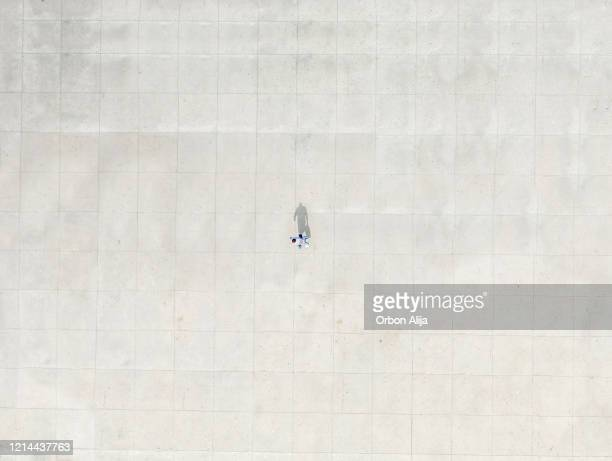 man walking alone to represent social distancing for covid-19 - town square stock pictures, royalty-free photos & images