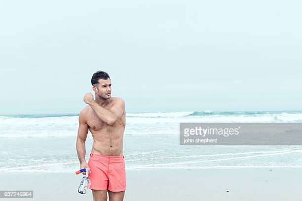 man walking along a beach in swim shorts with snorkel. - zwembroek stockfoto's en -beelden