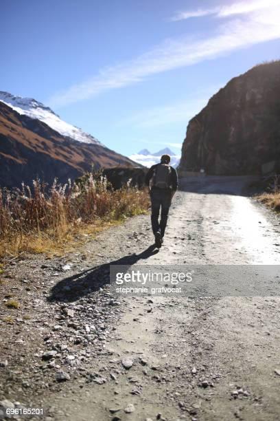 Man walking along a mountain trail, Switzerland