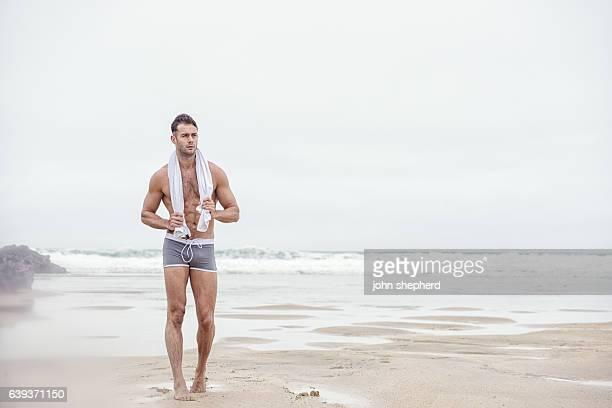 man walking along beach, grey swim shorts and towel. - behaart stock-fotos und bilder