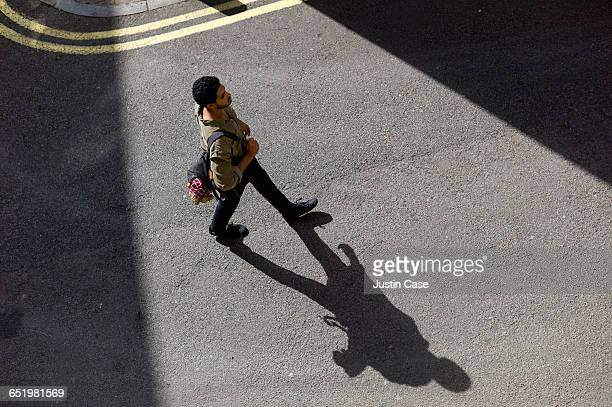 man walking along city streets - schaduw stockfoto's en -beelden