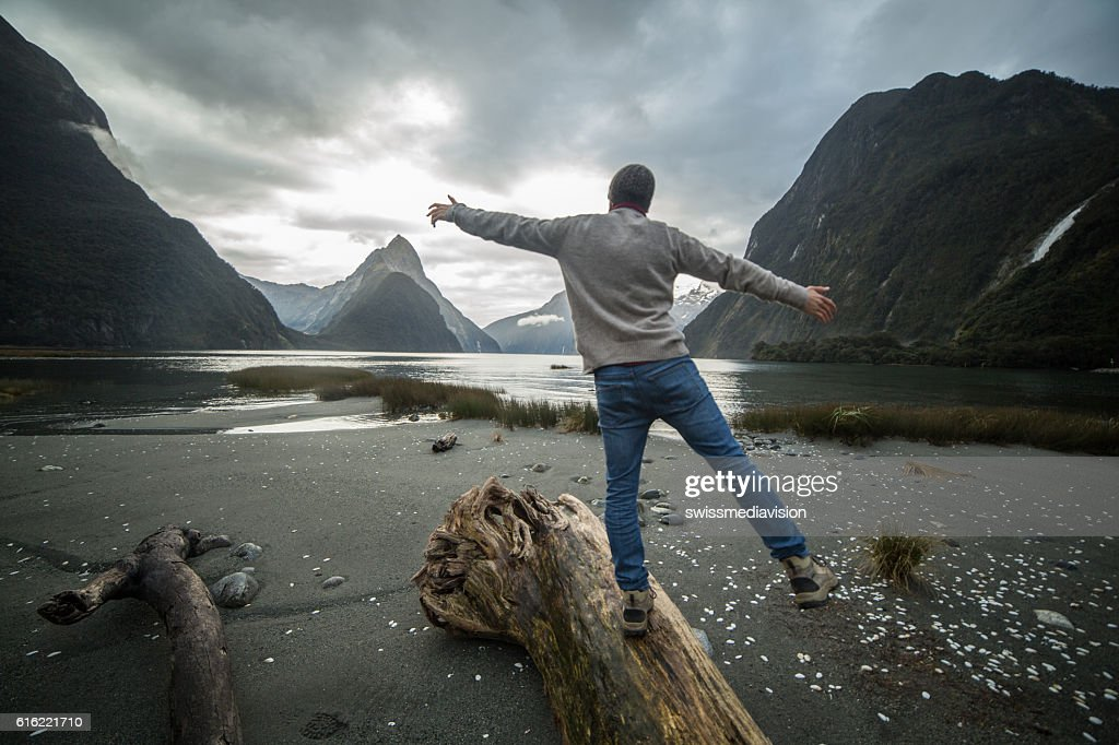Man walking along log in mountains, rear view : Stock Photo