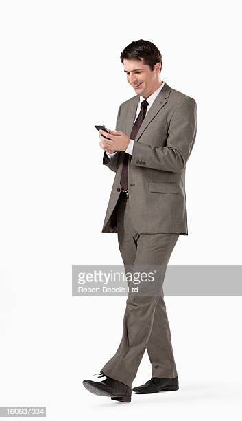 Man walking along looking at smart phone