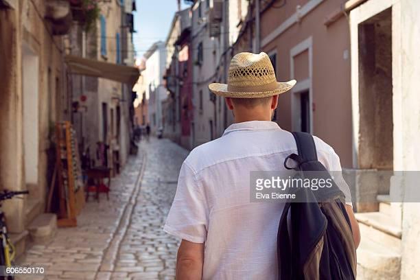 man walking along narrow, cobbled, town street in croatia - sac porté épaule photos et images de collection