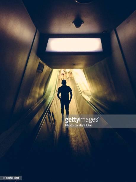 man walking along narrow tunnel - 陰謀 ストックフォトと画像