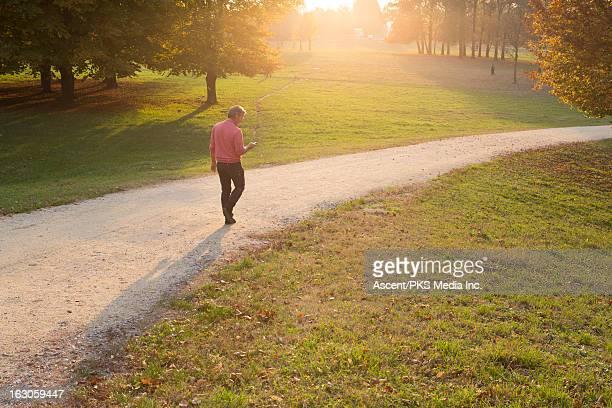 Man walking along path thru park