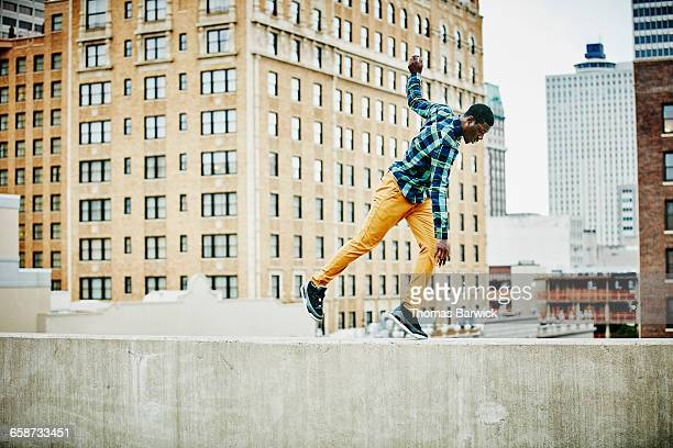 Man walking along rooftop ledge of building