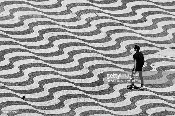 man walking along square paved with stone forming illusionist pattern - illusion stock pictures, royalty-free photos & images