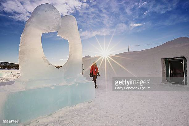 Man Walking Amidst House And Ice Sculpture Against Sky