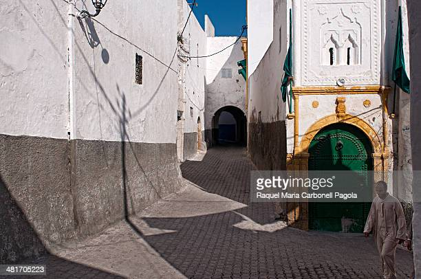 Man walking among beautiful white houses in the medina