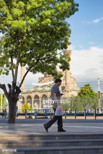 Mann zu Fuß und der Rechnungsprüfung mit einer BIM Einzelhandels-Discounter-Tasche in der hand