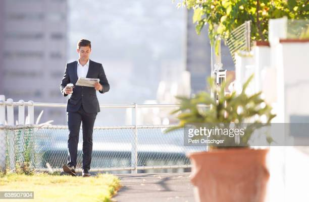 Man walking and reading the paper.