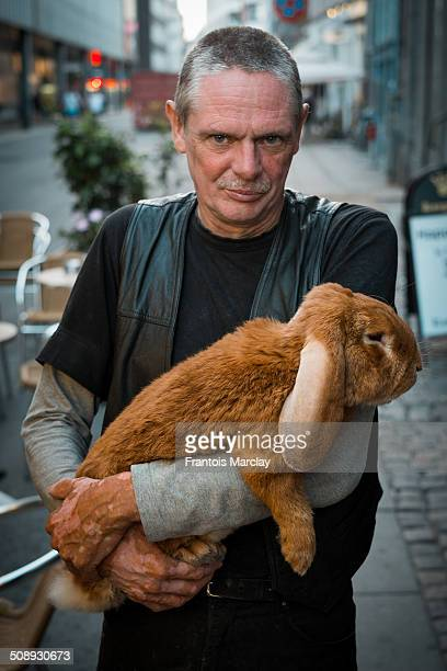 Man walking around the streets of Copenhagen with his giant ginger rabbit pet
