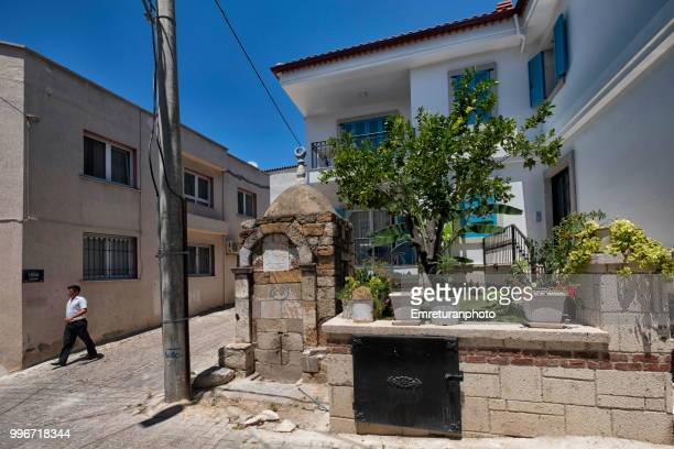 man walking at a street with a historic fountain,cesme. - emreturanphoto stock pictures, royalty-free photos & images