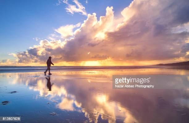 Man Walking At Beach With Reflection In Background.