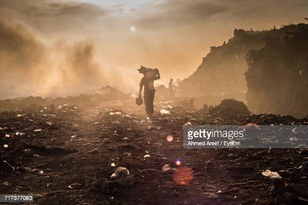 man walking at landfill - poverty stock pictures, royalty-free photos & images
