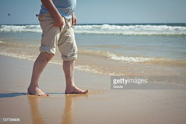 man walking at shore - rolled up trousers stock pictures, royalty-free photos & images