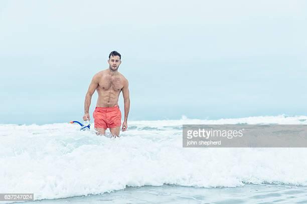 man walking at the shoreline holding snorkel mask. - vello pectoral fotografías e imágenes de stock