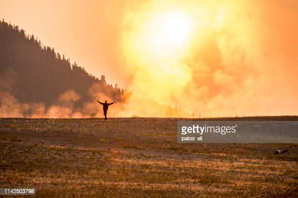 man walking at yellowstone park steam clouds on sunrise - caldera stock pictures, royalty-free photos & images