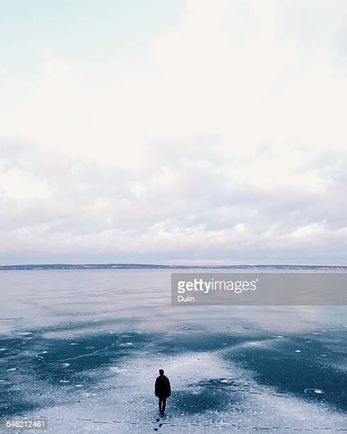 Man walking away across frozen lake