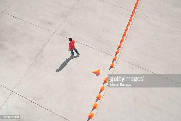 Hombre caminando lejos de fila de conos de tráfico con una