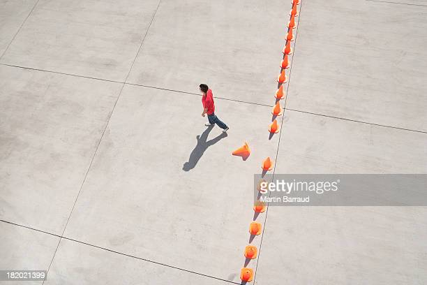 man walking away from row of traffic cones with one misplaced - traffic cone stock pictures, royalty-free photos & images