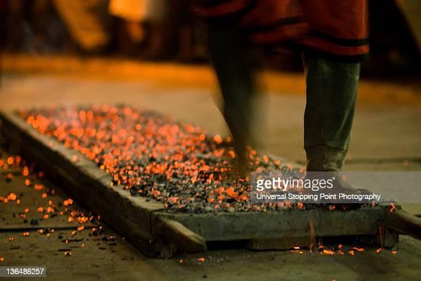 Man walking barefoot across bed of hot coals