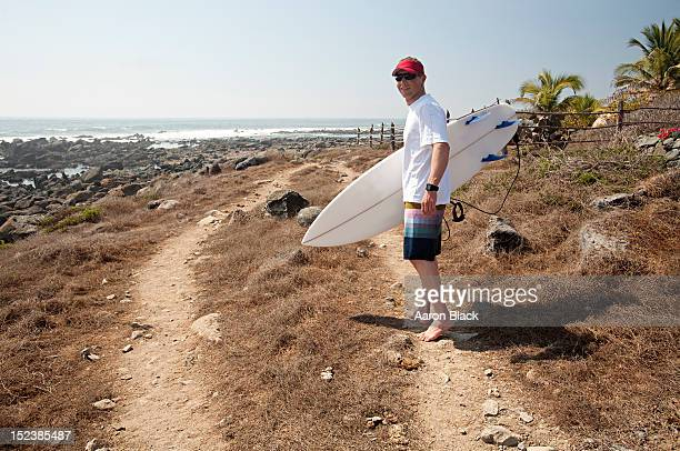 Man walking barefoot by the coast with a surfboard