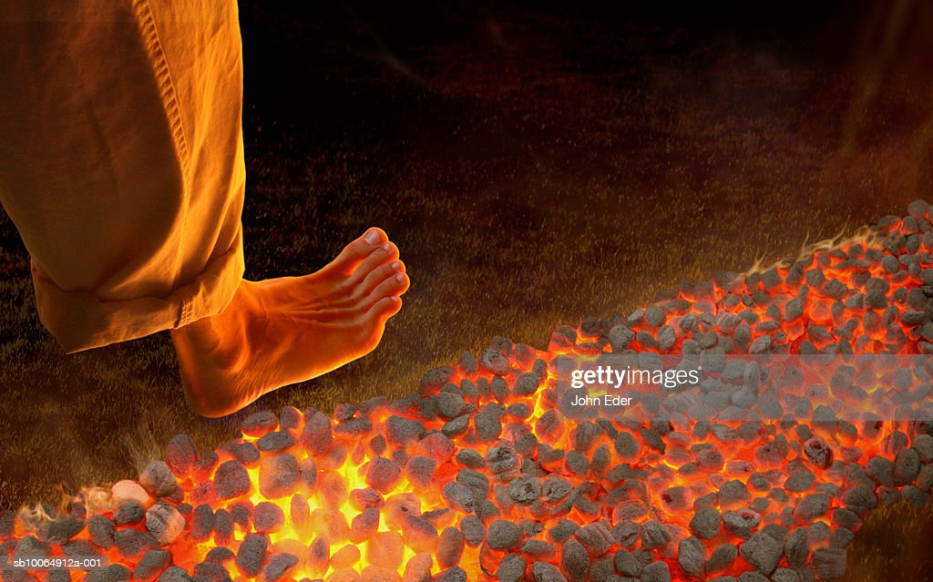 Man walking barefoot on hot coals, high angle view, close-up of foot : Foto de stock