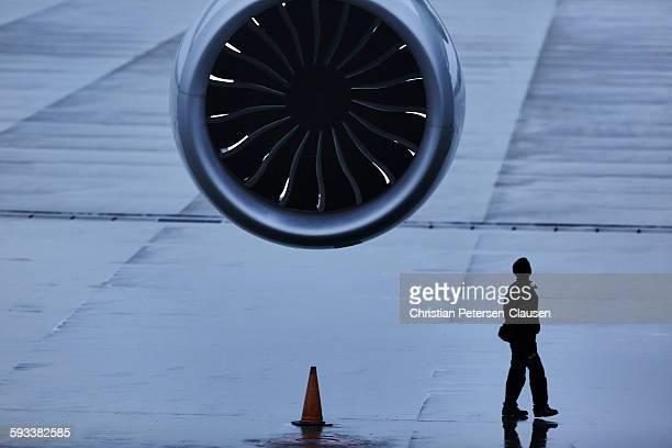 Man walking below Passenger Jet Aircraft engine
