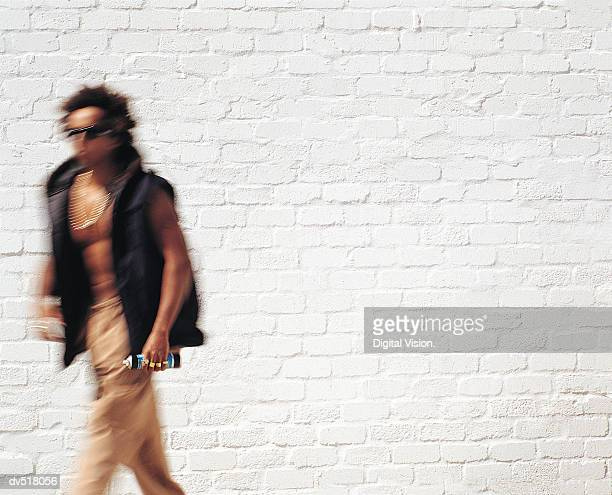 Man walking by a white wall