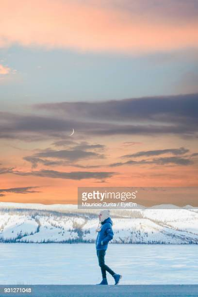 Man Walking By Frozen Lake Against Sky During Sunset