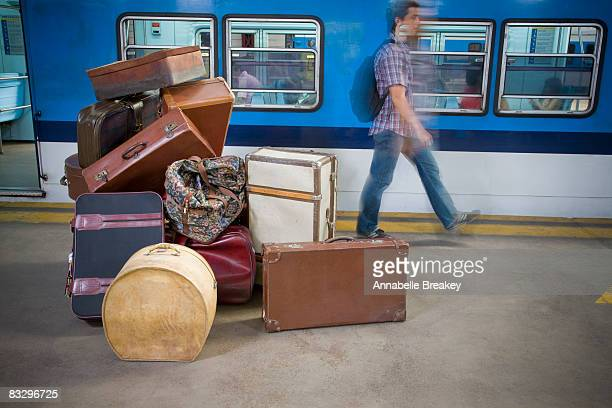Man walking by pile of luggage with motion.