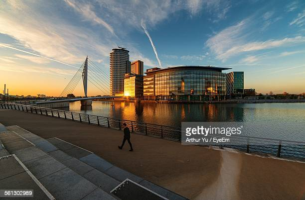 Man Walking By River And Modern Building Against Sky At Sunset