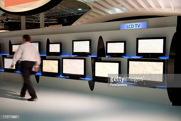Man walking by various displays of LCD TV