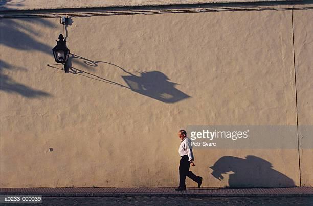 man walking by wall - pedone ruolo dell'uomo foto e immagini stock
