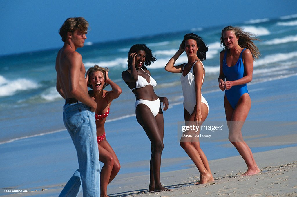 Man Walking By Women On The Beach Stock Photo