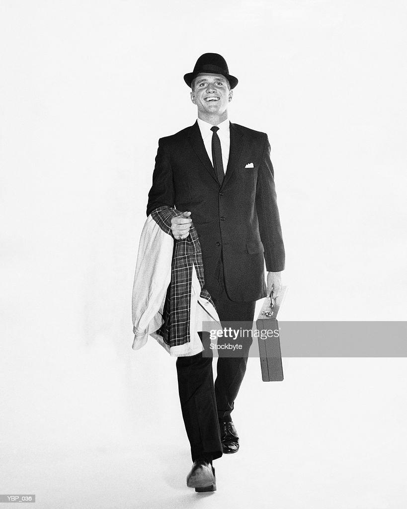Man walking, carrying briefcase and jacket : Stock Photo