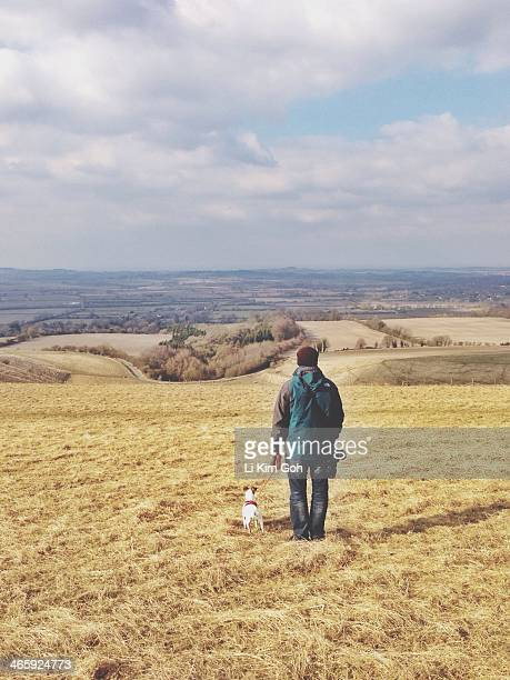 Man walking dog in the winter at Uffington White Horse Hill, England