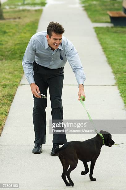 man walking dog on sidewalk, bending forward, smiling - bending over stock pictures, royalty-free photos & images