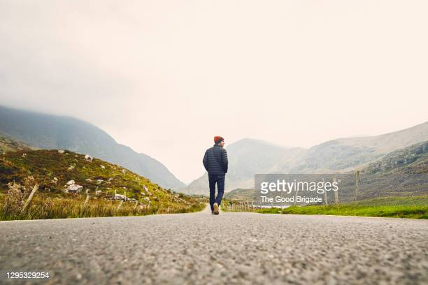 man walking down a country road in killarney, ireland - discovery stock pictures, royalty-free photos & images