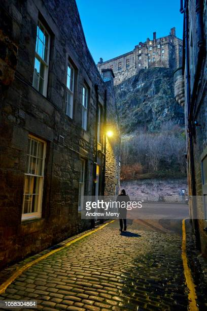 man walking down a narrow street, cobblestone alley with edinburgh castle on the horizon with blue night sky and bright yellow street light - historic district stock pictures, royalty-free photos & images
