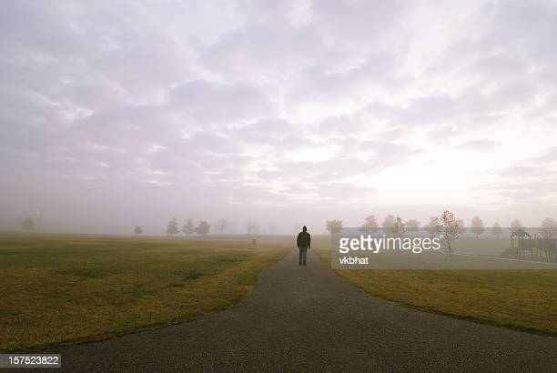 A man walking down a road into the fog