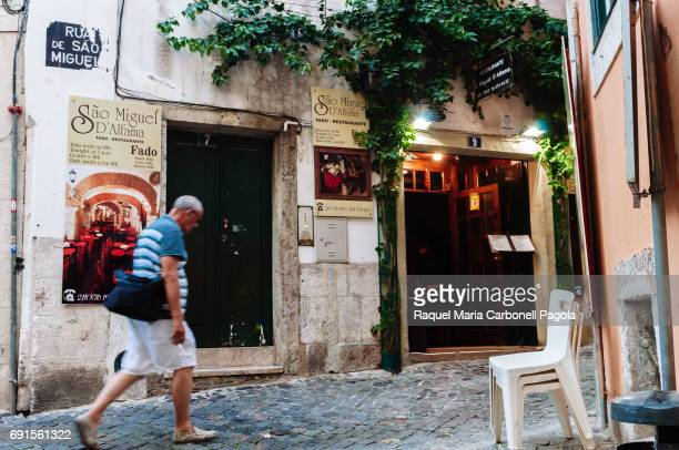 Man walking down a street passing by Sao Miguel d´Alfama Fado restaurant