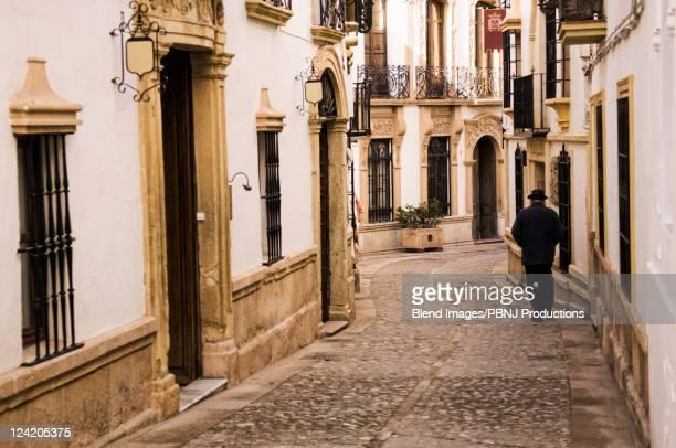 man walking down cobblestone alley in quaint village - carmona fotografías e imágenes de stock