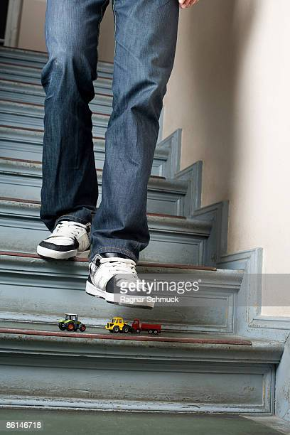 A man walking down stairs about to step on toy cars