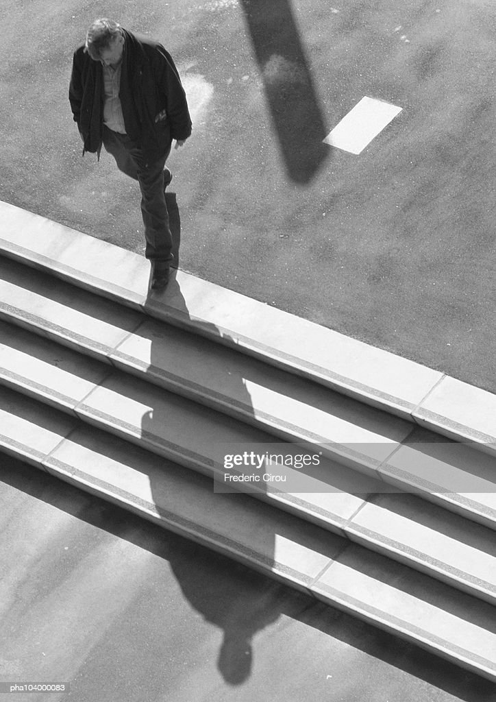 Man walking down stairs, elevated view, b&w : Stockfoto