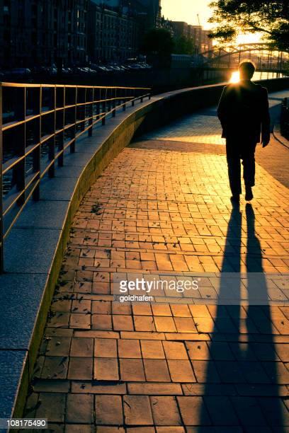 Man Walking Down Street at Sunset