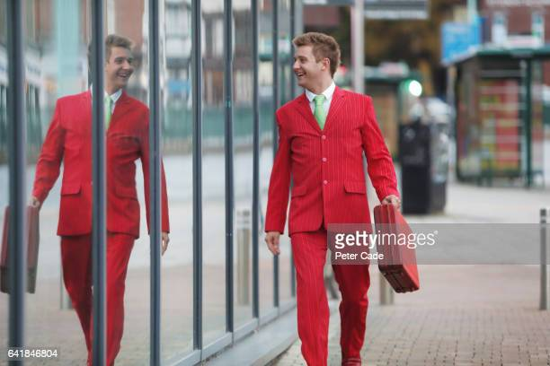 man walking down street in red suit, looking at reflection in glass window - red suit stock pictures, royalty-free photos & images